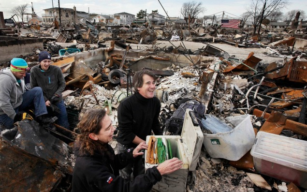 Rosemary McDermott and her husband Anthony Minor react as they open a safe containing a family genealogy they were able to salvage from the basement of her mother's home in the Breezy Point section of the Queens borough of New York, Thursday, Nov. 15, 2012. A fire destroyed more than 100 homes in the oceanfront community during Superstorm Sandy. On the left are Todd Griffin and Kevin Striegle, volunteers with Adventures in Missions, who helped find the safe beneath the rubble. (AP Photo/Mark Lennihan)